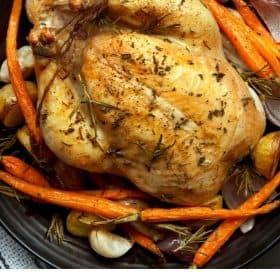 Whole cooked chicken with carrots and onions