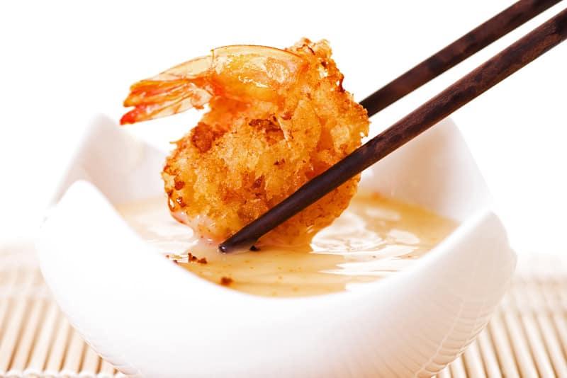 dipping shrimp in bang bang sauce