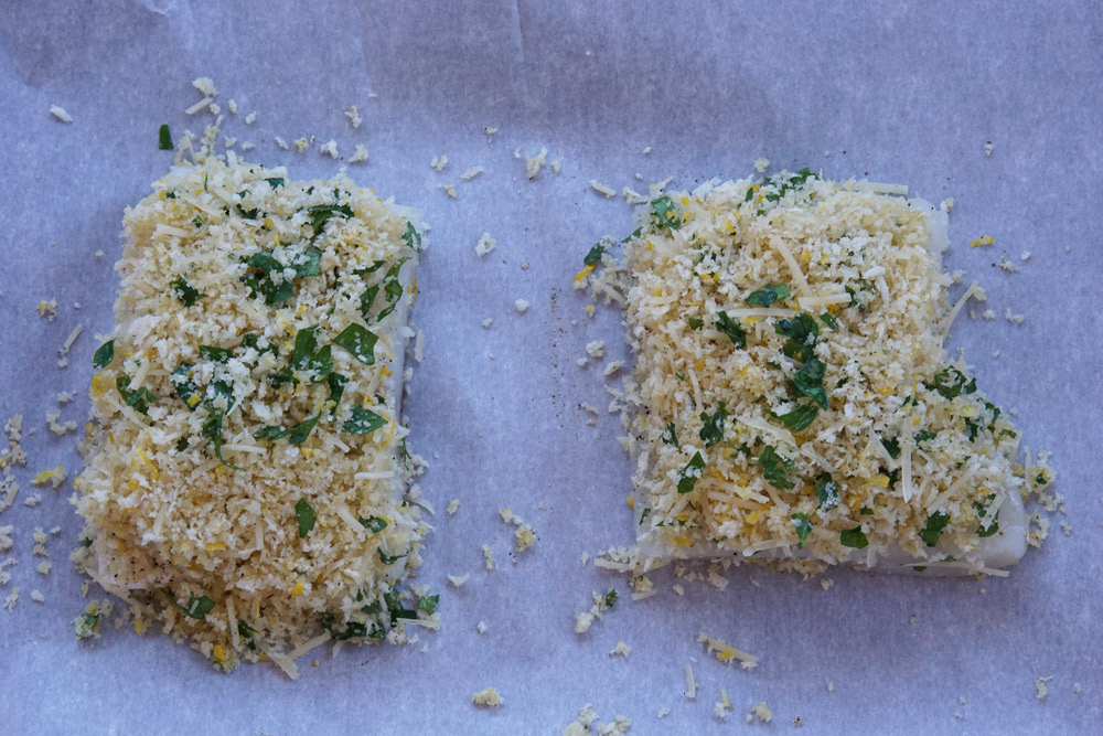Uncooked cod fillets with parmesan topping