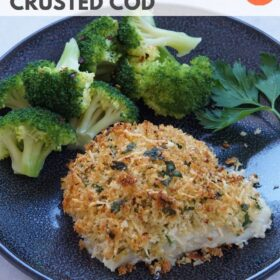 Finished parmesan crusted cod on a plate with steamed broccoli