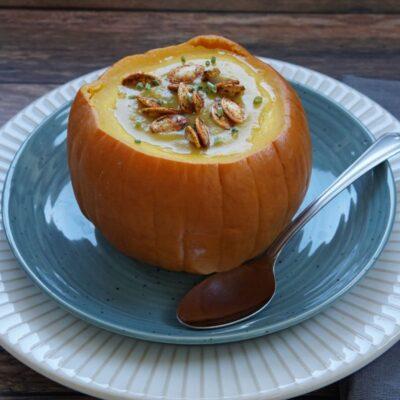 Pumpkin soup in a pumpkin with pumpkin seeds on top