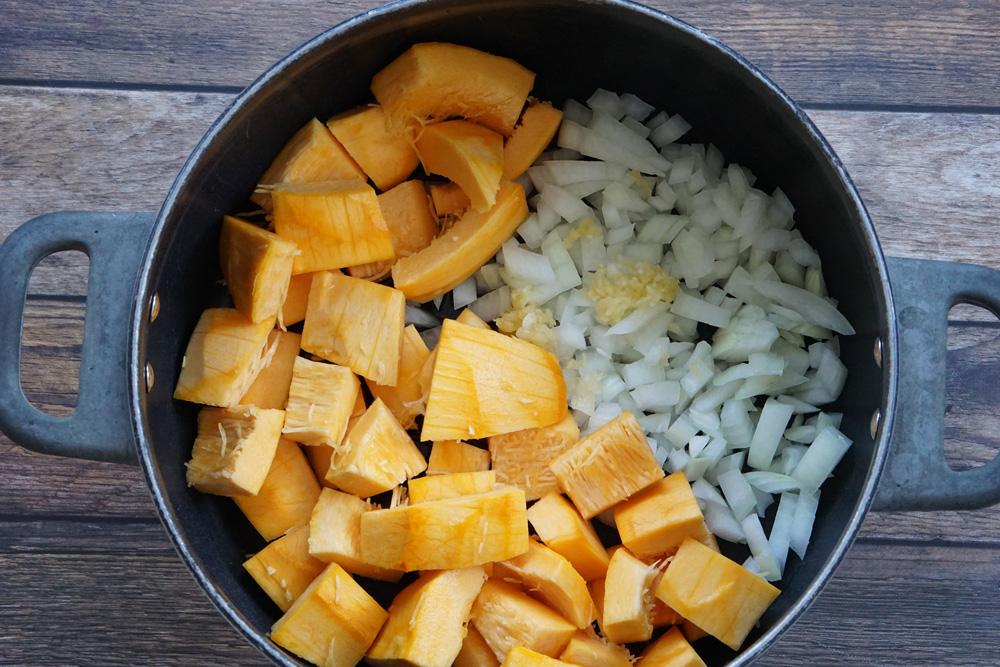 Raw pumpkin, onion and garlic in a pot