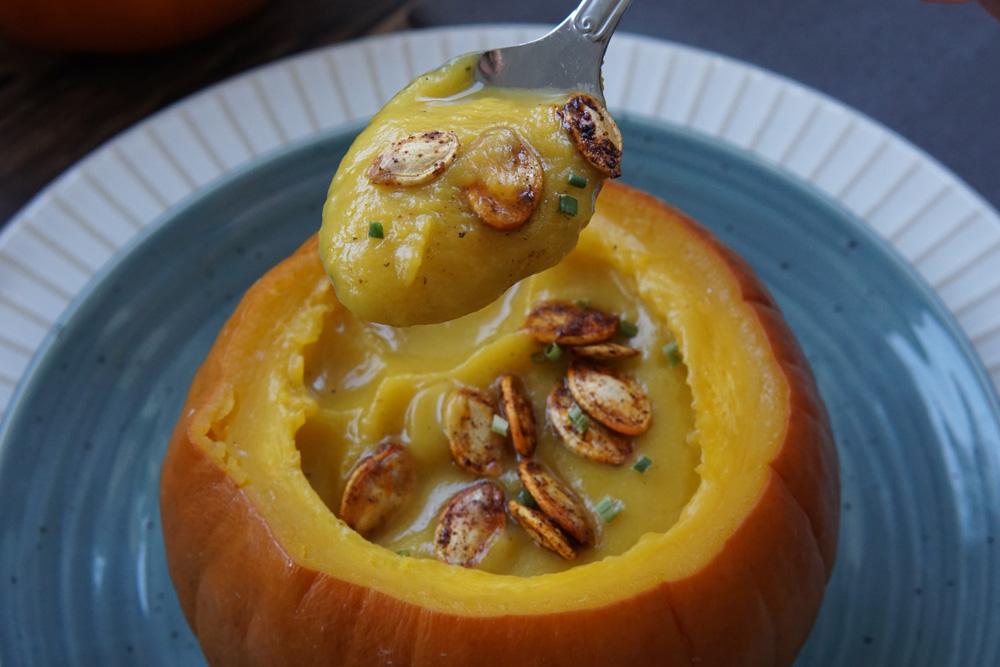 A spoon full of Pumpkin soup in a pumpkin with pumpkin seeds on top